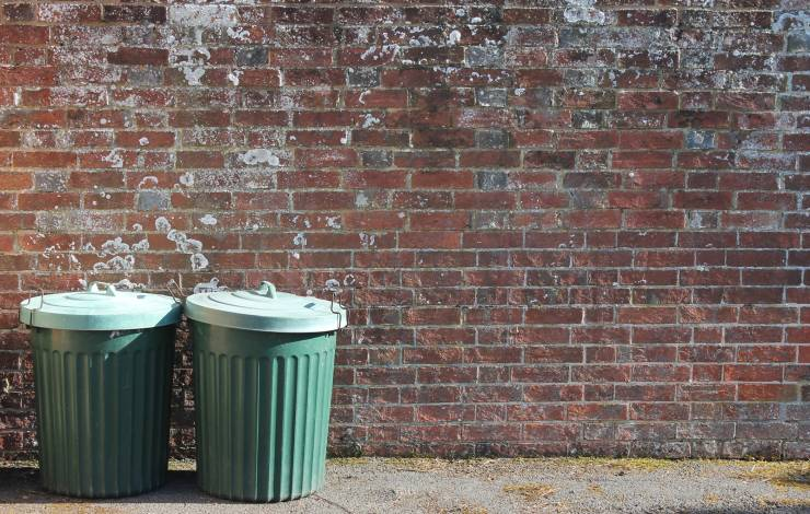 two green trash cans​ against a brick wall