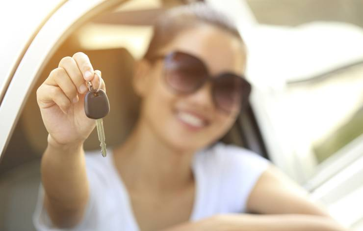 woman sitting happily in a new car, showing off the key