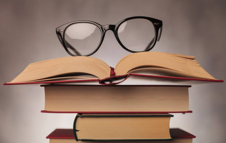 pair of glasses on top of a pile of books , shot in studio