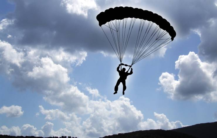 silhouette of person landing a parachute