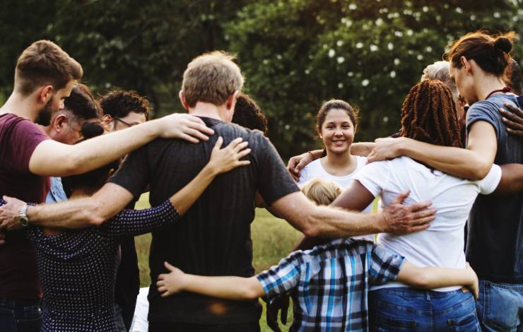Group of people huddle together in the park