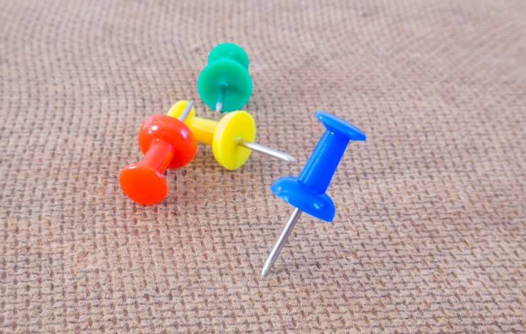colorful thumbtacks on bulletin board