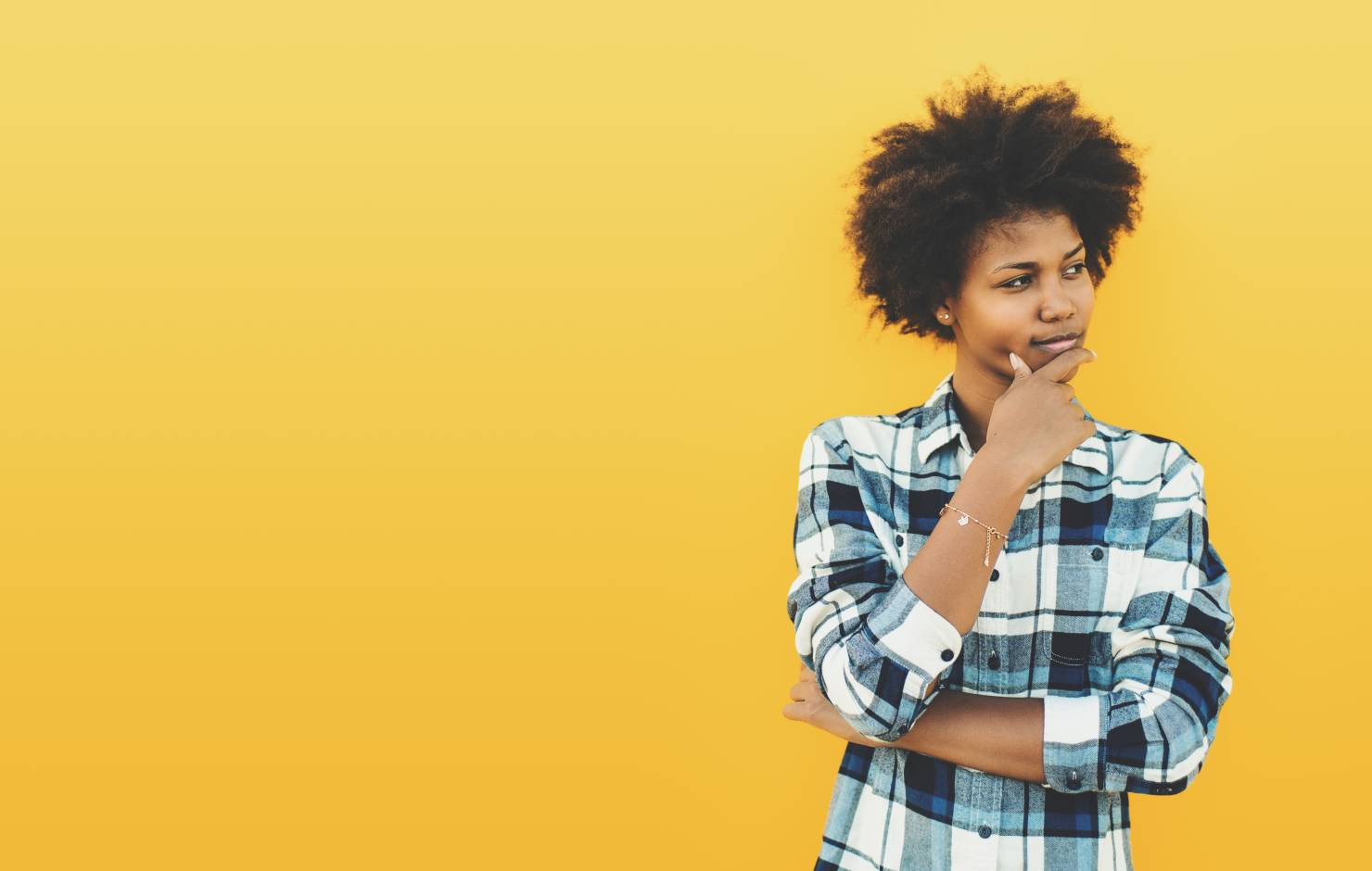 young woman thinking in front of a yellow wall