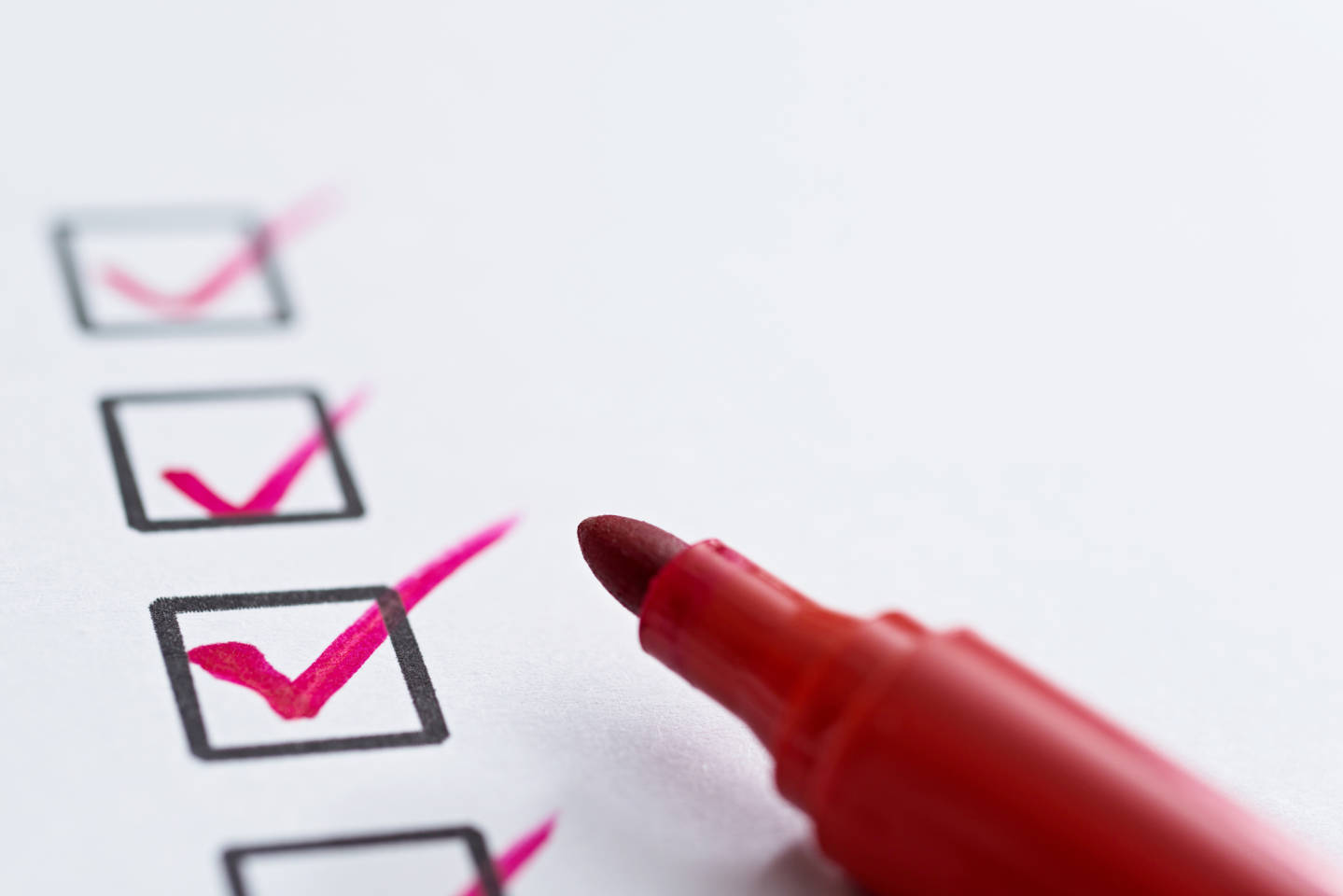 checklist with red pen on white background