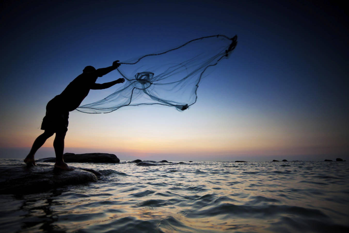 man throwing fishing net into the ocean at sunset