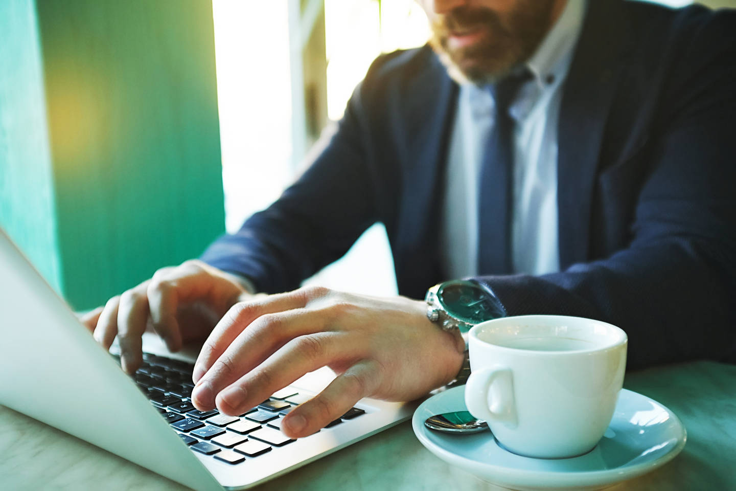 Hands of businessman typing with teacup near by