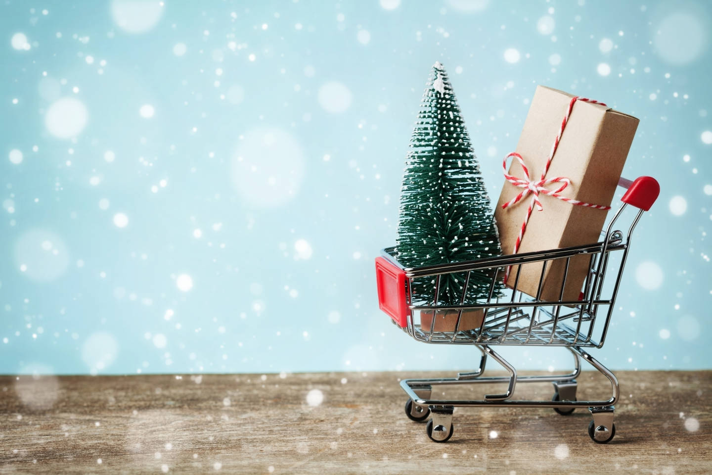 toy shopping cart with christmas tree and gift with snow falling around
