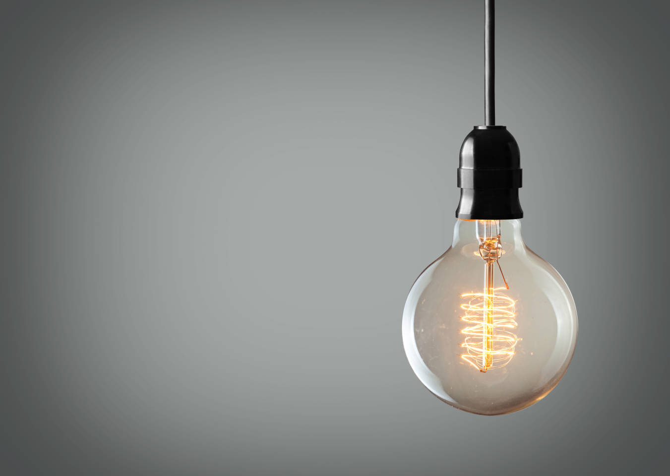 single lightbulb hanging in front of blank wall