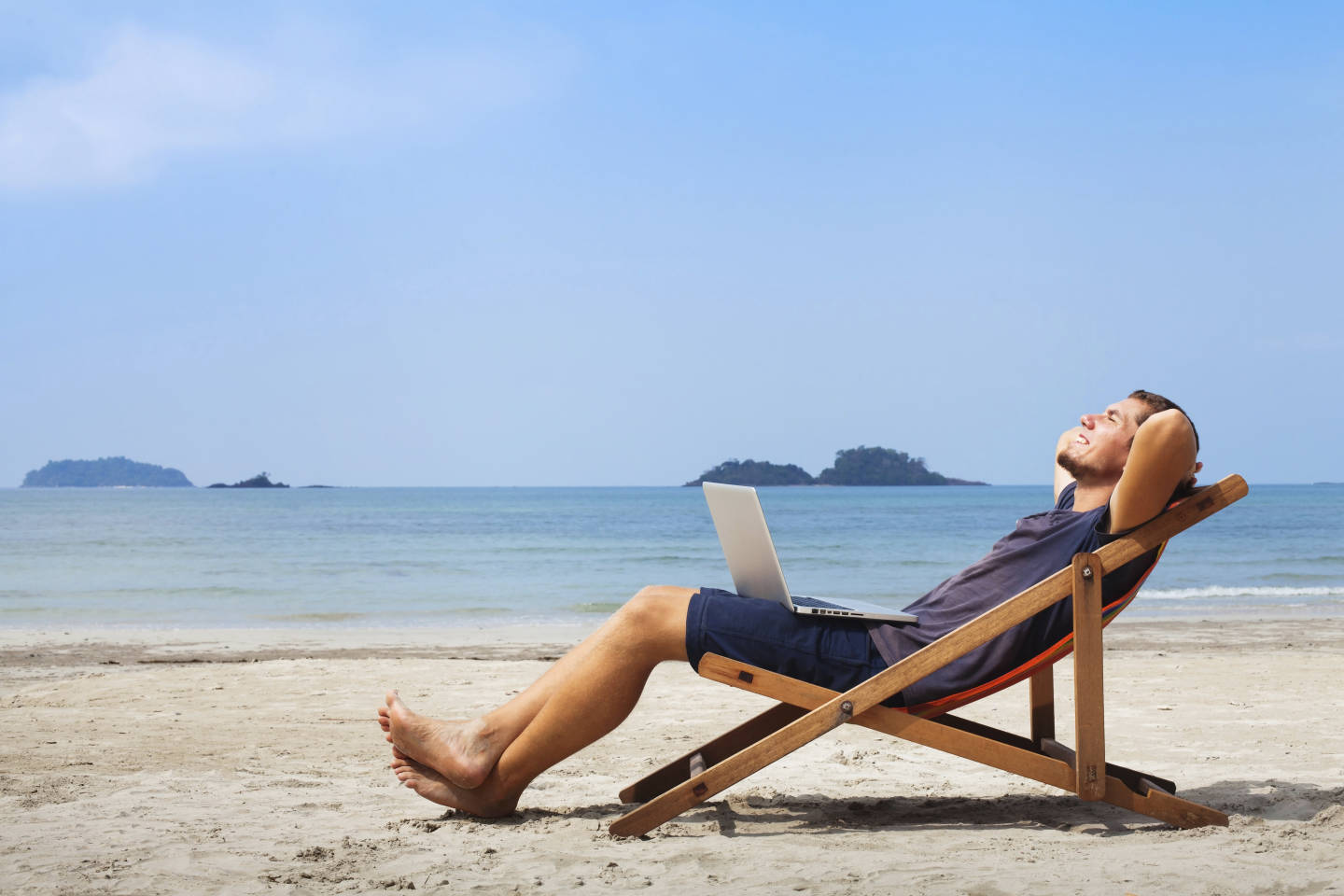 man chilling on beach with laptop