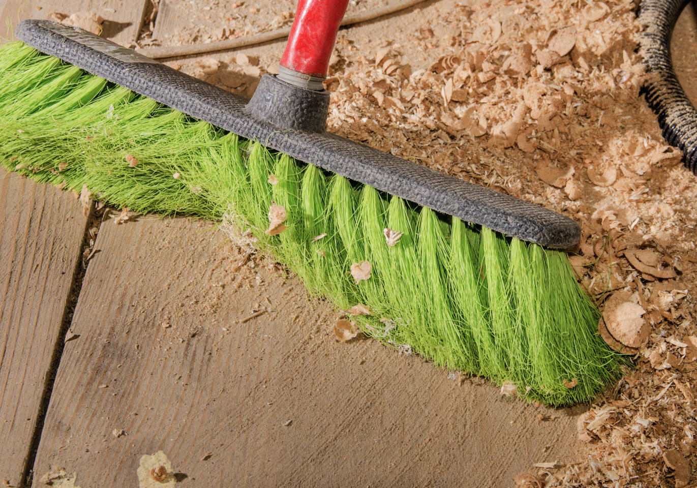 sweeping up sawdust with a shop broom