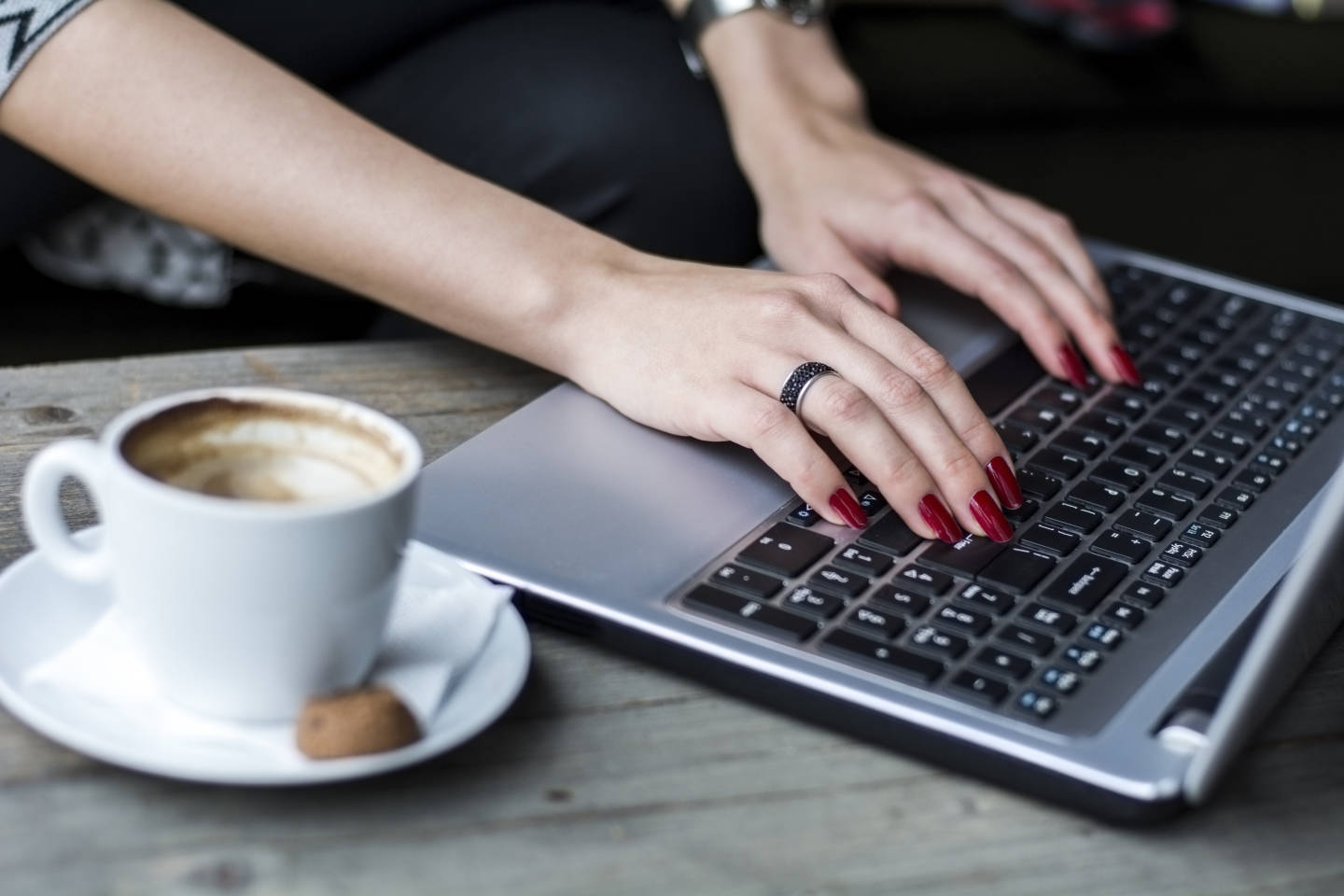 woman typing on computer with a cup of coffee.