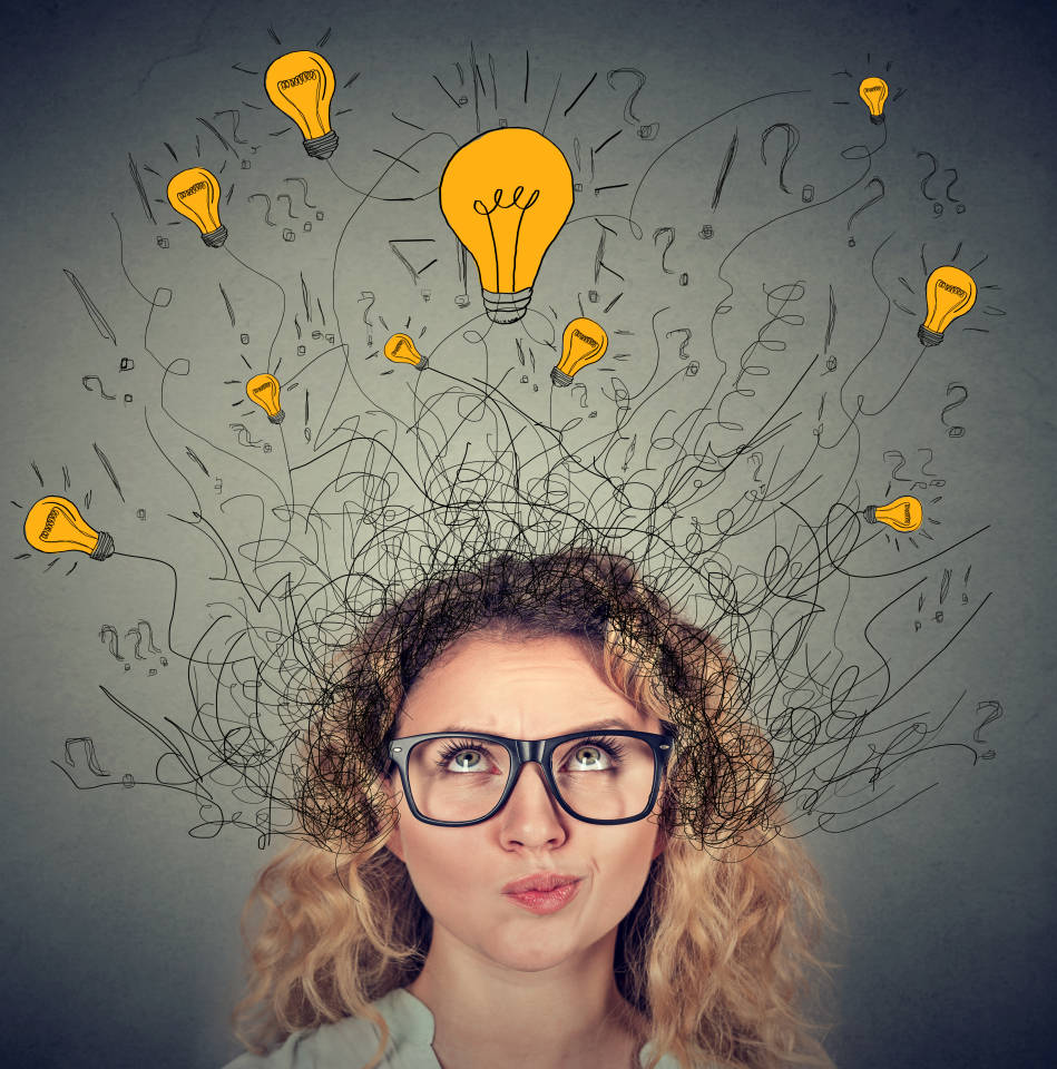 Thoughtful woman in glasses with many ideas light bulbs above head looking up isolated on gray wall background. Eureka creativity concept