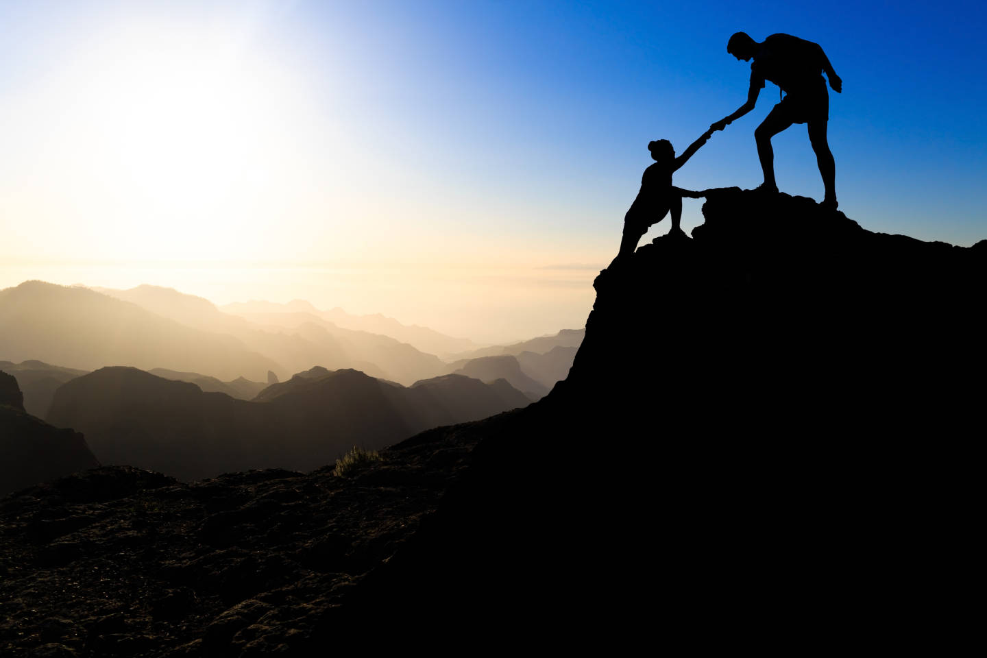 man helping woman up a mountain