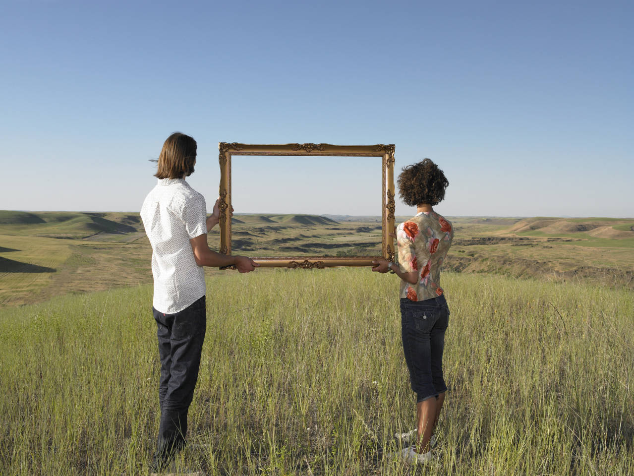 couple standing in an open field holding an empty picture frame