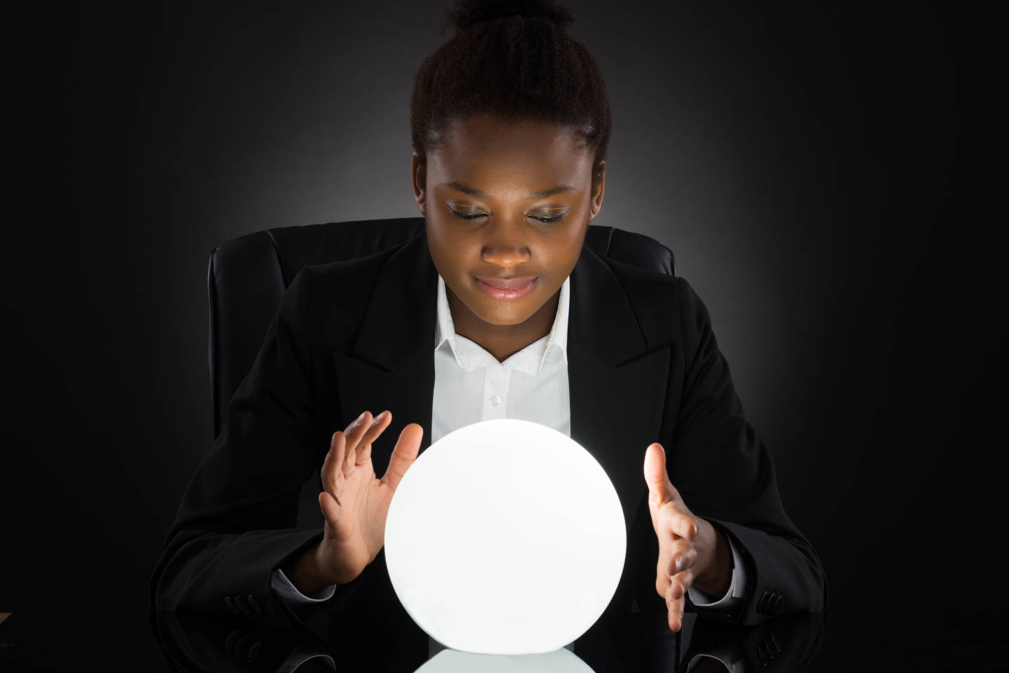 Young African Businesswoman Predicting Future With Crystal Ball On Desk Over Black Background