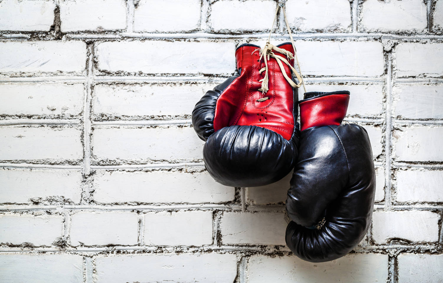 pair of red and black boxing gloves on white brick background