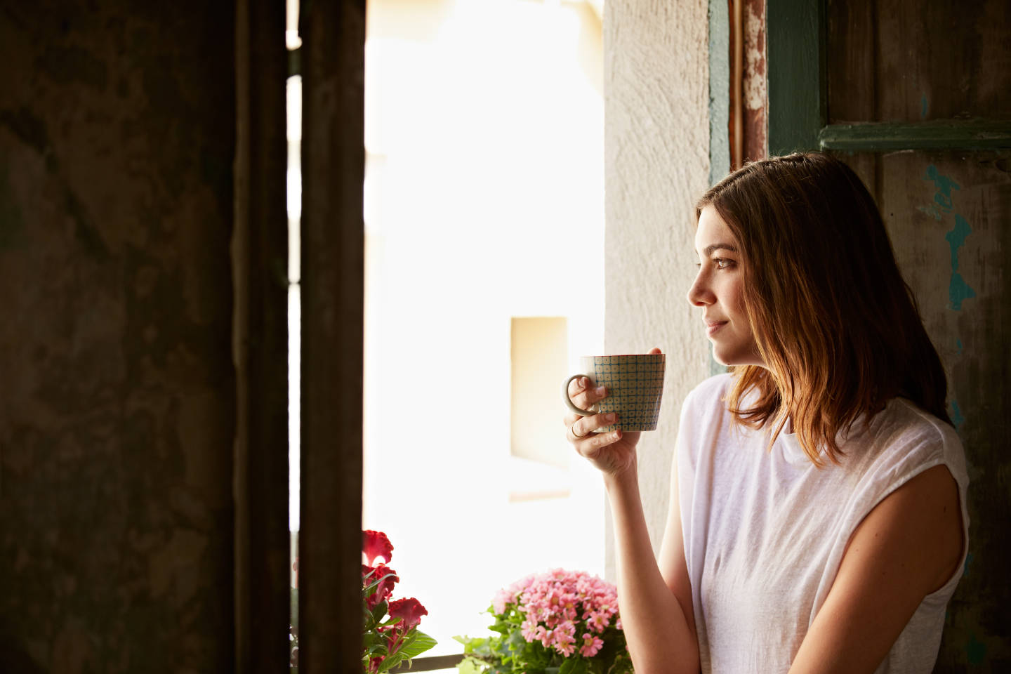 woman drinking coffee while looking out window