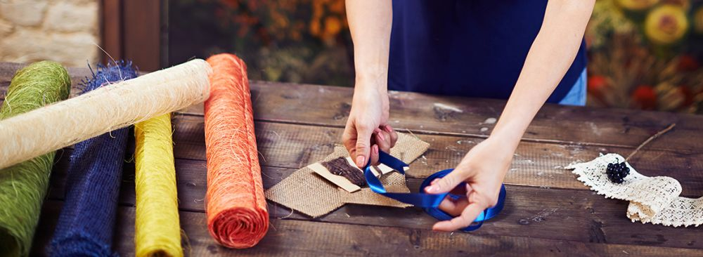 Woman's hands measuring ribbon on crafts table