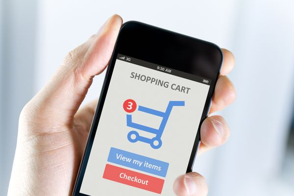 hand holding cell phone with shopping cart in screen