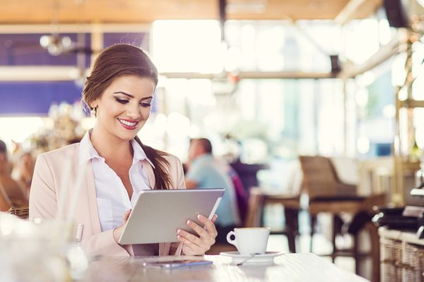 Woman in a restaurant looking at tablet and smiling