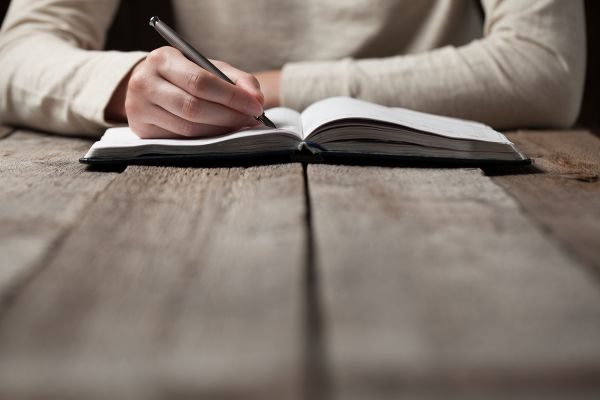 close up of a person writing in a notebook