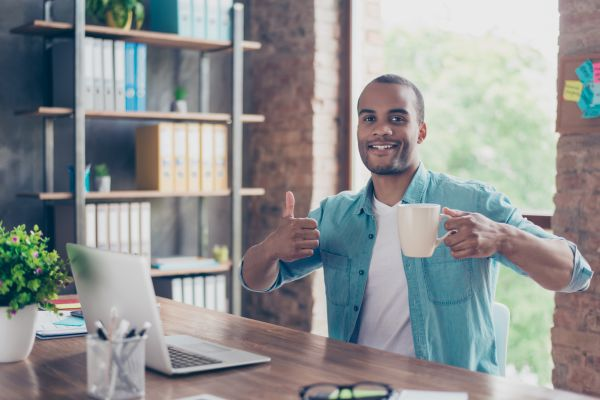 Guy giving a thumbs up while drinking coffee and working on laptop