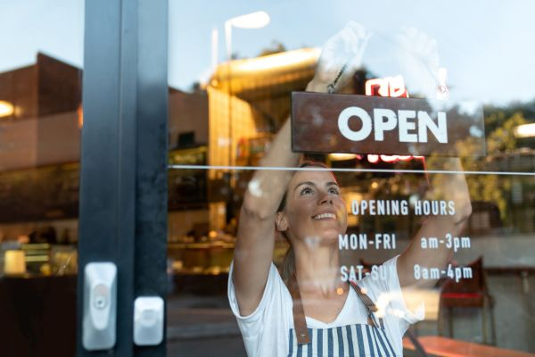 Woman hanging an open sign on business front door