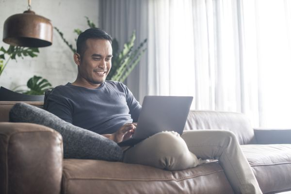 Man sitting on a couch looking at laptop and smiling