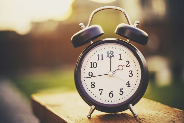 Close up of a clock with a blurred sunset background