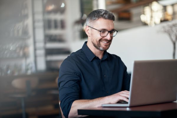 male small business owner happily working on laptop
