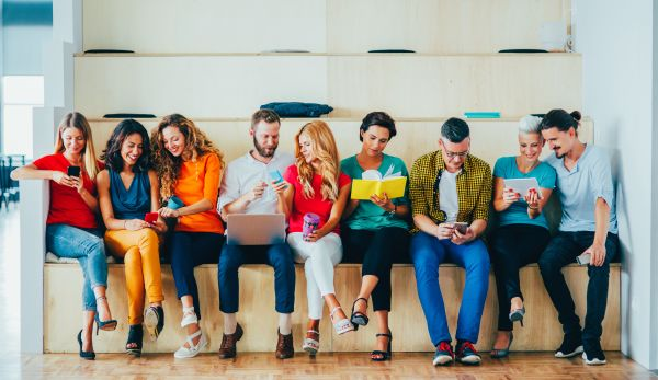 A row of people with similar intrests sitting together and looking at content on various mobile devices