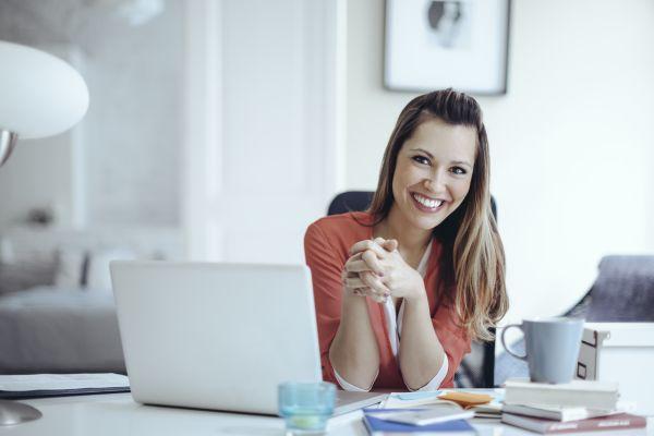 Confident woman at home office desk wtih laptop