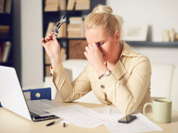 Woman working at desk concerned about debt