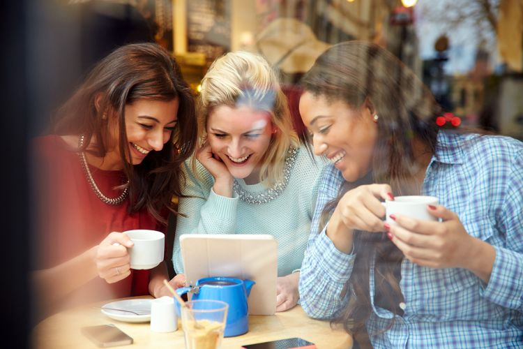 Three women huddled together looking at tablet in coffee shop